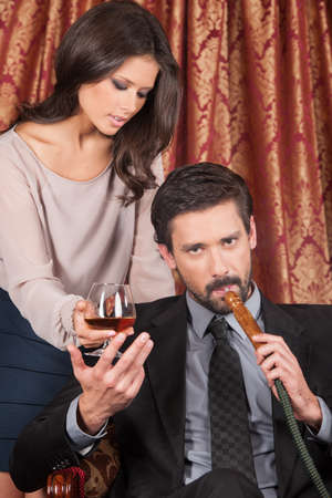 tomando refresco: mujer seductora de pie detr�s del hombre en el caf� �rabe. hombre inhalar hookah y tomando un vaso de whisky Foto de archivo