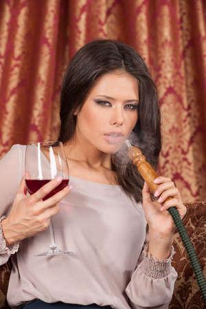 chica fumando: Mujer joven hermosa que exhala la cachimba. chica fumando shisha turco y beber