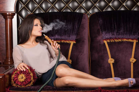inhaling: Beautiful young woman inhaling hookah. girl smoking shisha lying on sofa in cafe Stock Photo