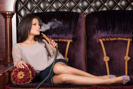 Mooie jonge vrouw het inademen waterpijp. meisje roken shisha liggend op een sofa in cafe Stockfoto