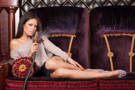 Mooie jonge vrouw, liggend en waterpijp roken. verleidelijk en sexy meisje roken en ontroerende benen Stockfoto