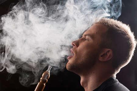 Close-up der Mann das Rauchen traditionelle Wasserpfeife. Mann Ausatmen Rauch auf schwarzem Hintergrund