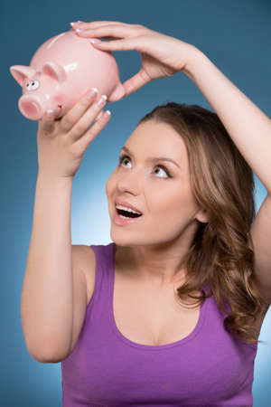 smiling woman looking at piggy bank. Young woman looking for money in piggy bank  photo