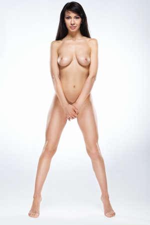 Aantrekkelijke naakte vrouw staande tip tenen op een witte achtergrond. volledige beeld van mooie donkerharige meisje die zichzelf Stockfoto