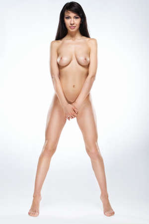 Attractive naked woman standing tip-toed on white background. full image of beautiful dark-haired girl covering herself