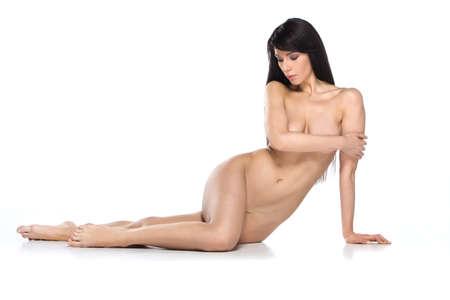 mujer desnuda sentada: Atractiva belleza morena desnuda con la piel limpia. joven chica de pelo oscuro que se sienta en el fondo blanco