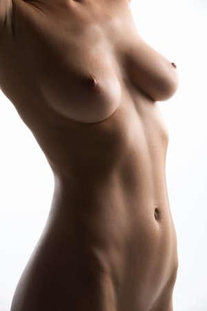 desnudo de mujer: mujer joven desnuda delante de fondo blanco. hermoso pecho desnudo y el vientre de la chica joven