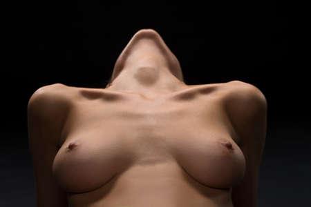 desnudo artistico: pecho desnudo con los pezones de la mujer joven. sexy chica desnuda vista de cerca sobre fondo negro