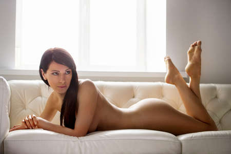brunette naked: Naked brunette posing on white leather sofa. dark-haired naked woman lying and looking away