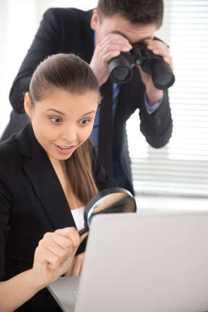 Businesswoman observing laptop with magnifying glass. man standing behind girl and holding binoculars photo