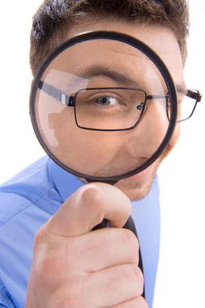 Nieuwsgierige mens die door vergrootglas. Portret van een jonge man op zoek door vergrootglas op een witte achtergrond