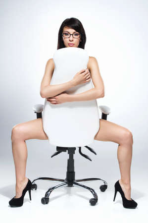 naked woman sitting: beautiful naked dark-haired woman sitting on white chair. nude young girl sitting and looking at camera Stock Photo