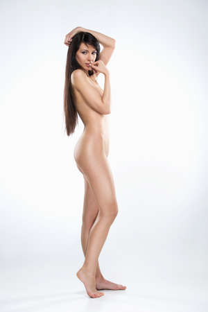 side view of attractive naked woman standing tip-toed on white background. full image of beautiful dark-haired girl biting fingers