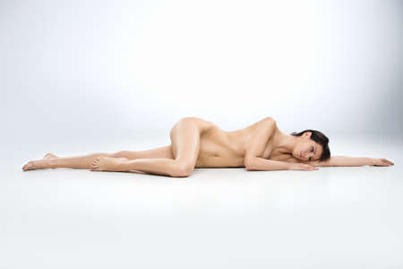 woman naked body: Young attractive woman laying naked on white background. full image of dark-haired girl resting on floor