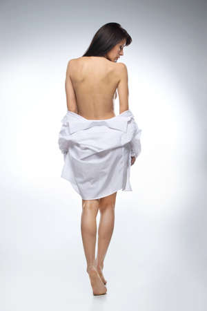 full image of beautifull woman in shirt on white background. back view of dark-haired naked girl looking down Stock Photo