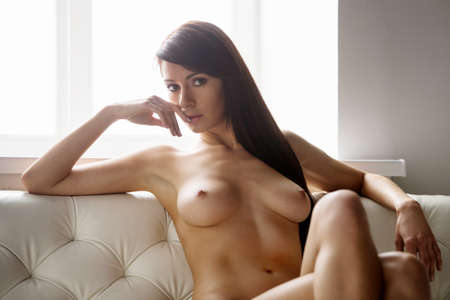 bare breast: Naked brunette posing on white leather sofa. dark-haired naked woman sitting and looking into camera