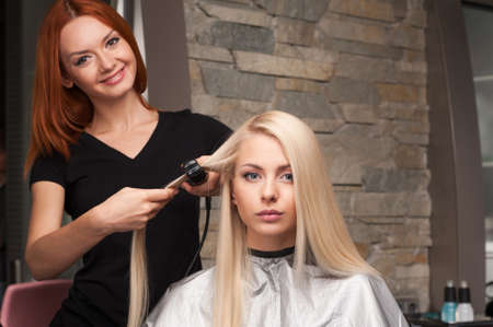 beauty parlor: Happy young woman getting new haircut by hairdresser at parlor. redhead hairdresser straightening clients hair in beauty salon Stock Photo