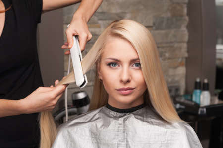 Großansicht auf junge Frau immer neuen Haarschnitt durch Friseur im Salon. Friseur Begradigung Haar des Klienten im Schönheitssalon