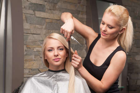 horizontal haircut: Happy young woman getting new haircut by hairdresser at parlor. blond hairdresser cutting clients hair in beauty salon Stock Photo