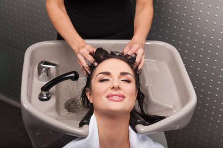 Smiling woman having her hair washed at hairdressers. Hairdresser washing hair of woman in barber shop. photo