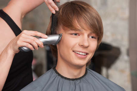 Female hairdresser cutting hair of man client using trimmer. happy man sitting in hair salon and smiling photo