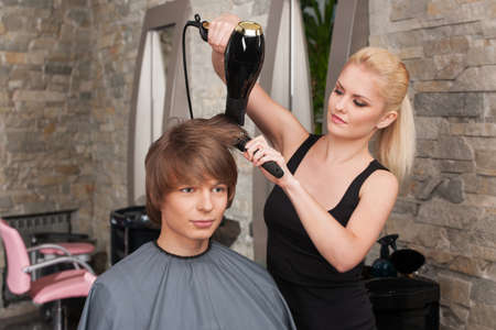 Blond female hairdresser drying hair of man client. young attractive man sitting in hair salon photo
