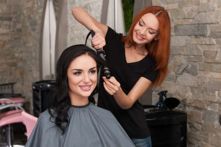 Drying woman's hair after giving new haircut at parlor. redhead girl drying dark-haired girl hair and smiling Stock Photo