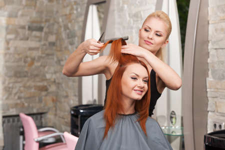 Happy young woman getting a new haircut. Beautiful young hairdresser giving new haircut to female customer at parlor Stock Photo