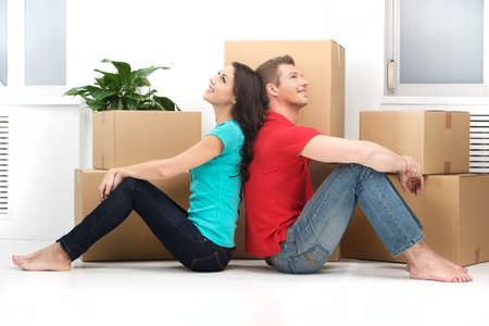 happy young couple moving in new home. man and woman sitting on floor back to back Stock fotó - 32577526