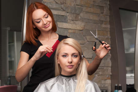 Happy young woman getting new haircut by hairdresser at parlor. redhead hairdresser cutting clients hair in beauty salon photo