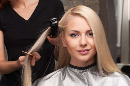 closeup on happy young woman getting new haircut by hairdresser at parlor. hairdresser straightening client's hair in beauty salon Standard-Bild