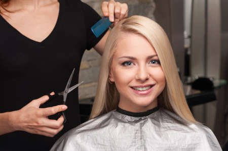 blonde: Happy young woman getting new haircut by hairdresser at parlor. hairdresser cutting clients hair in beauty salon