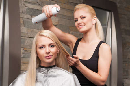blond hairdresser applying spray on clients hair and looking into camera. Female hairdresser works on woman hair in salon