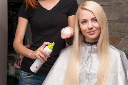redhead hairdresser applying mousse on client's hair. Female hairdresser works on woman hair in salon Foto de archivo
