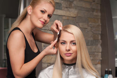 color swatch: Blond girl selecting tone of hair in hair salon. Female client and blond hairdresser choosing shades of colour in salon