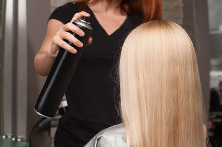 Back view of woman getting new haircut by hairdresser at parlor. redhead hairdresser cutting client's hair in beauty salon