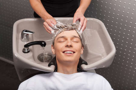 happy client: Close-up of young smiling caucasian man having his hair washed. Portrait of happy client with closed eyes at salon