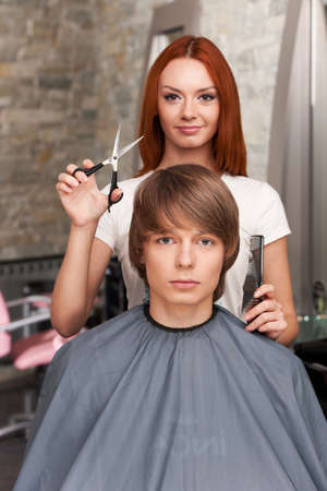 Female hairdresser cutting hair of man client and looking into camera. closeup on handsome man sitting in hair salon and looking into camera photo