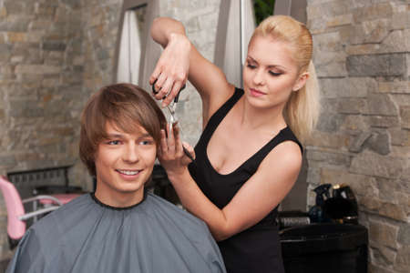 Blond female hairdresser cutting hair of man client. closeup on happy man sitting in hair salon and smiling photo