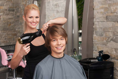 Blond female hairdresser drying hair of man client. profile of happy man sitting in hair salon and smiling photo