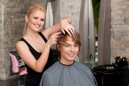blond hairstylist applying hair mousse spray. young attractive man sitting in hair salon photo