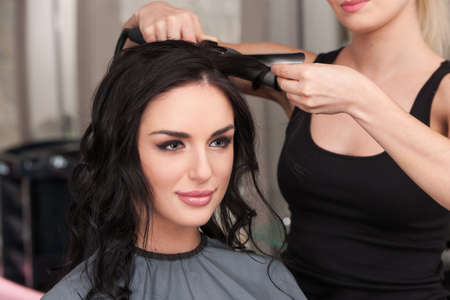 young woman getting her hair curled by stylist at parlor. Beautiful young hairdresser giving new haircut to female