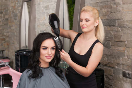 Beautician blow drying woman's hair after giving new haircut at parlor. blond girl drying dark-haired girl hair and smiling