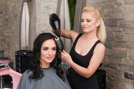 Het haar van schoonheidsspecialiste föhnen vrouw na het geven van nieuwe kapsel op salon. blond meisje drogen donkerharige meisje haar en glimlachend