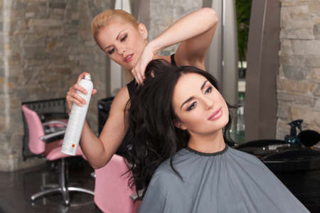 Young female hairdresser applying spray on client's hair. Female hairdresser works on woman hair in salon Stock Photo