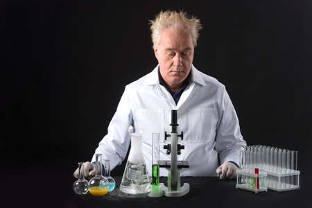 boiling tube: serious clinician studies in laboratory and looking at flask and bubble. adult man sitting on black background at table with microscope Stock Photo