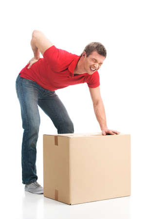 man back pain: man dressed in casual clothing hurt his back lifting large box. young man suffering from back pain isolated on white background