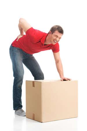 man, gekleed in casual kleding gekwetst zijn rug tillen grote doos. jonge man die lijden aan pijn in de rug op een witte achtergrond