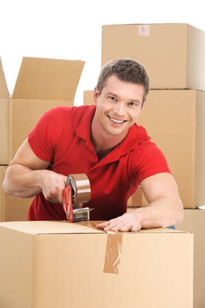 sealing tape: Young man packing boxes to move in new flat. smiling male with roll of brown packaging