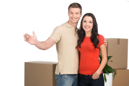 couple celebrating new home with keys and moving boxes. Happy couple moving into new apartment.